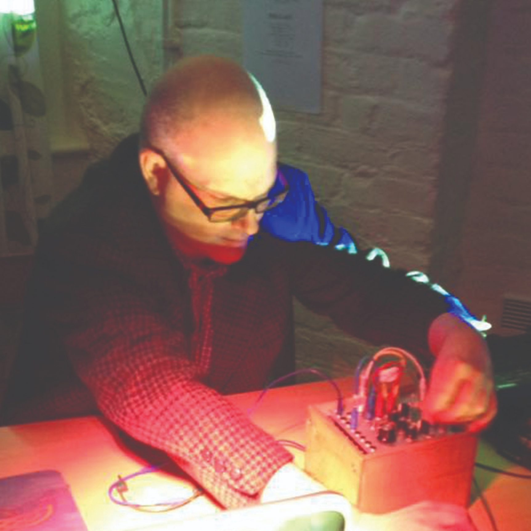 Dafydd Roberts (white man with shaved head, wearing glasses and a jacket) altering the settings on a small, electronic device