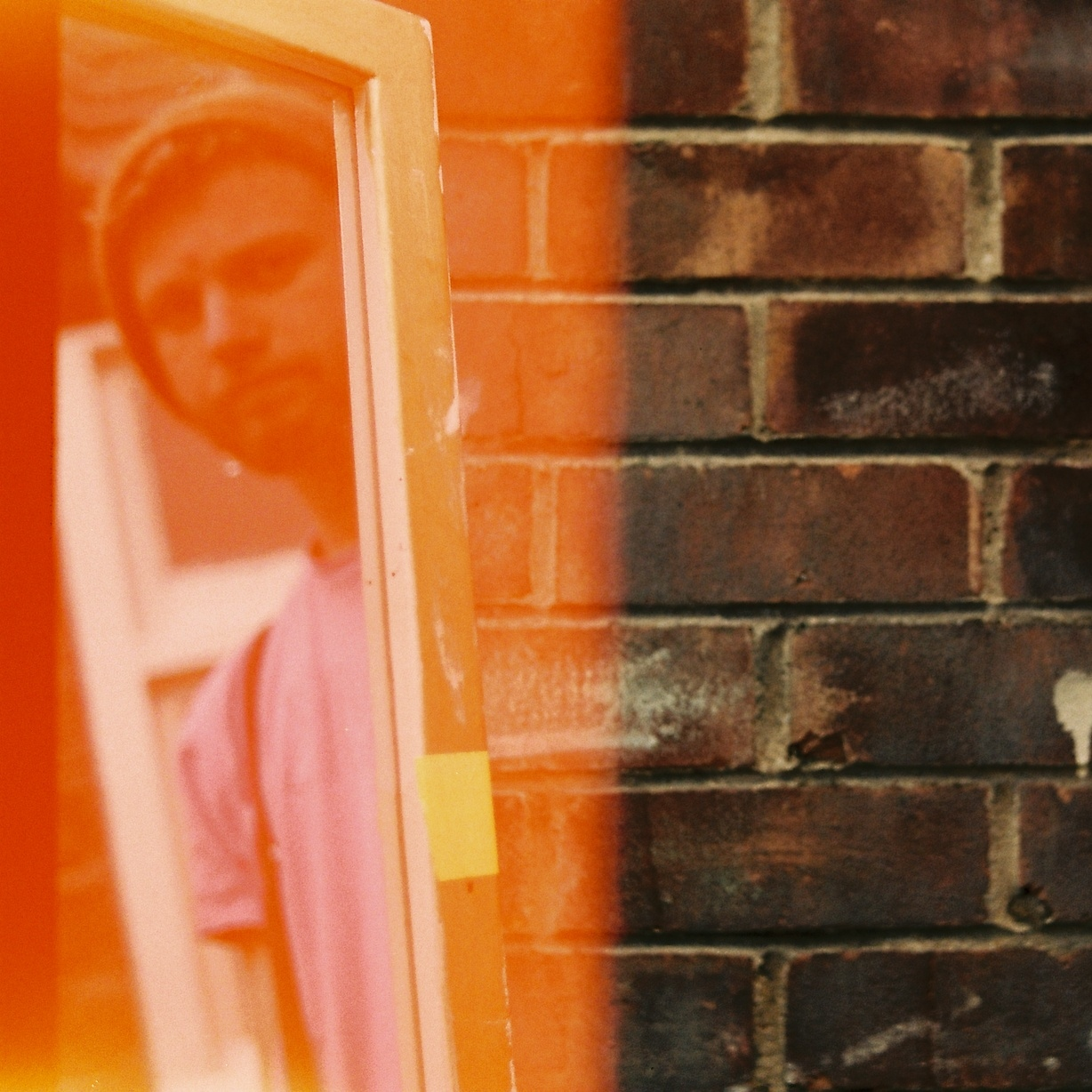 James Mcilwrath (young white man in beanie and pink t-shirt) reflected in a window