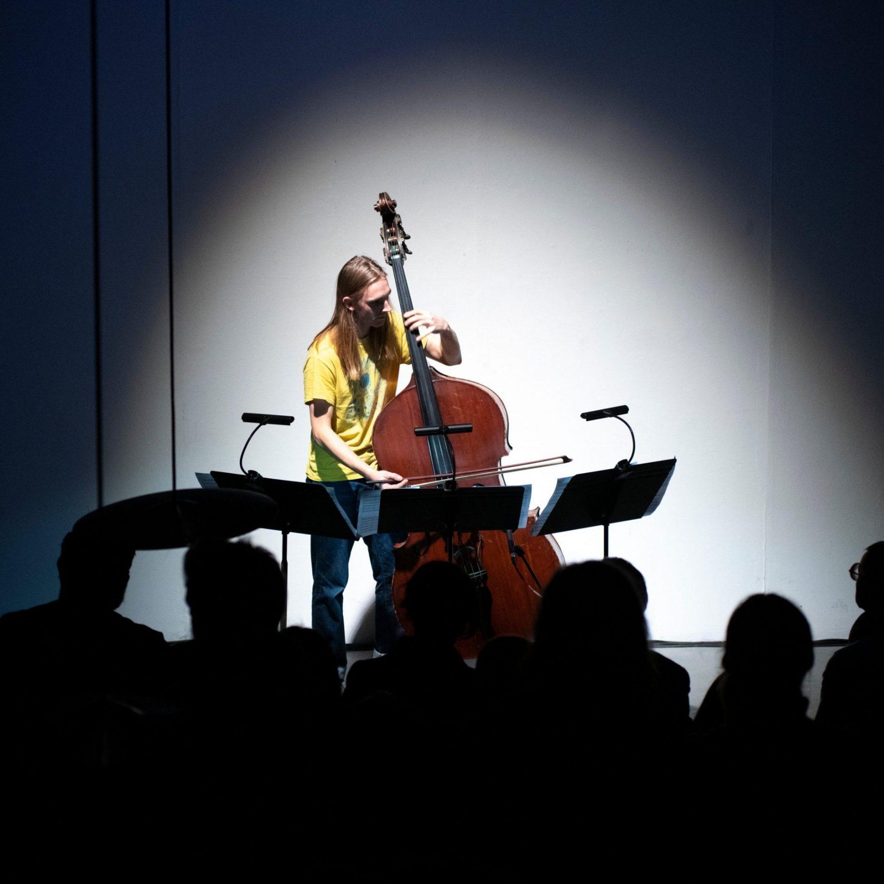 Otto playing bass under spotlight